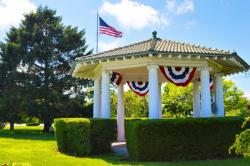 Gazebo with American flag flying above it in background